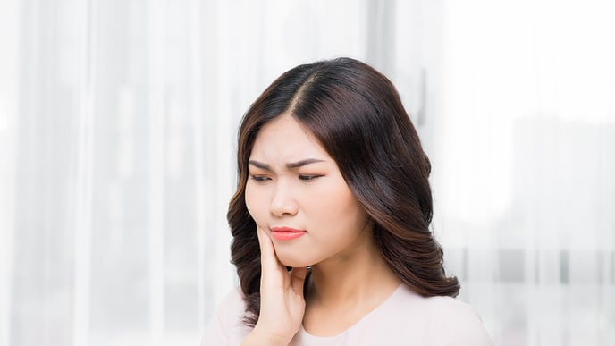 woman holding jaw due to tooth pain