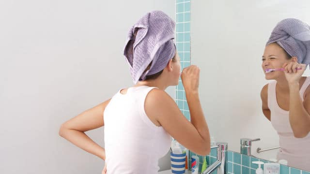 a woman is brushing her teeth in front of the mirror