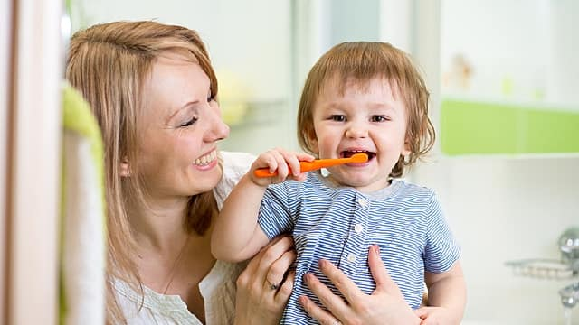 mother is helping her kid brushing teeth to prevent tooth decay