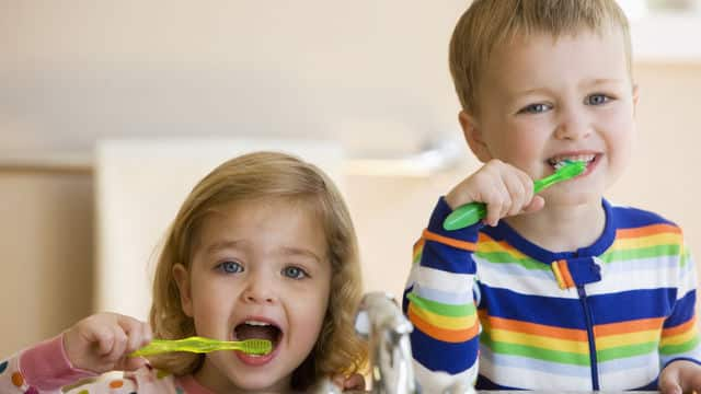 Toddlers brushing and flossing their teeth